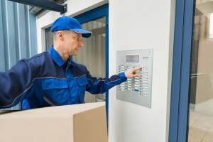 Delivery Man With Cardboard Box Pressing Button Of Intercom To Enter Building